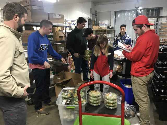 Group photo placing food in bins and inventorying.