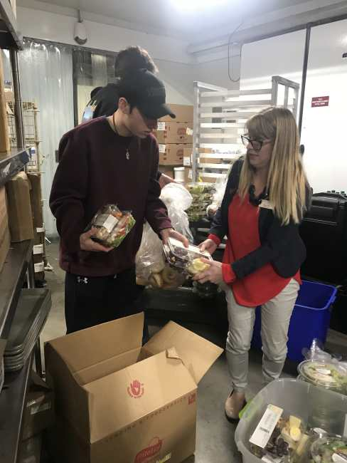 Robert and Brooke putting packed food in boxes.