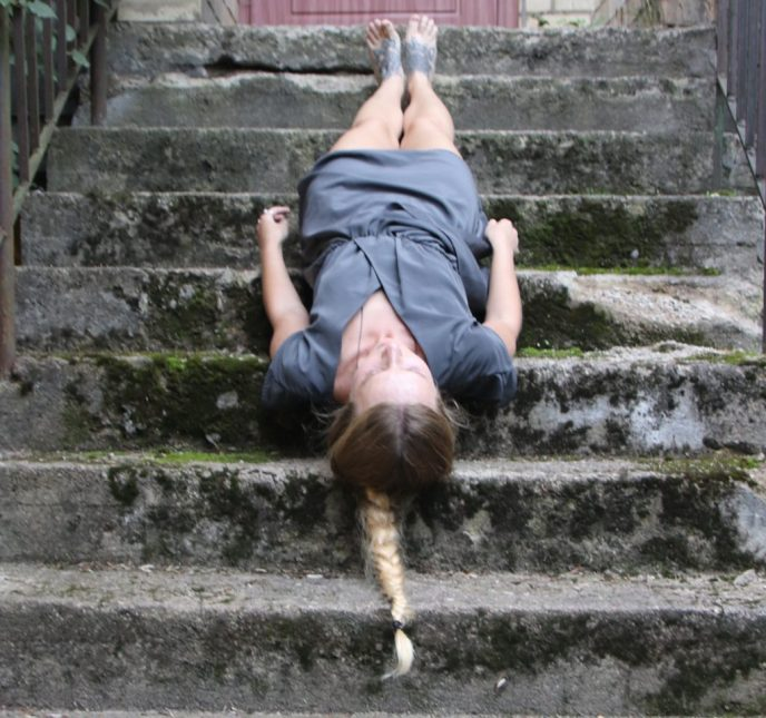 young female artist lying on concrete covered in moss stairs