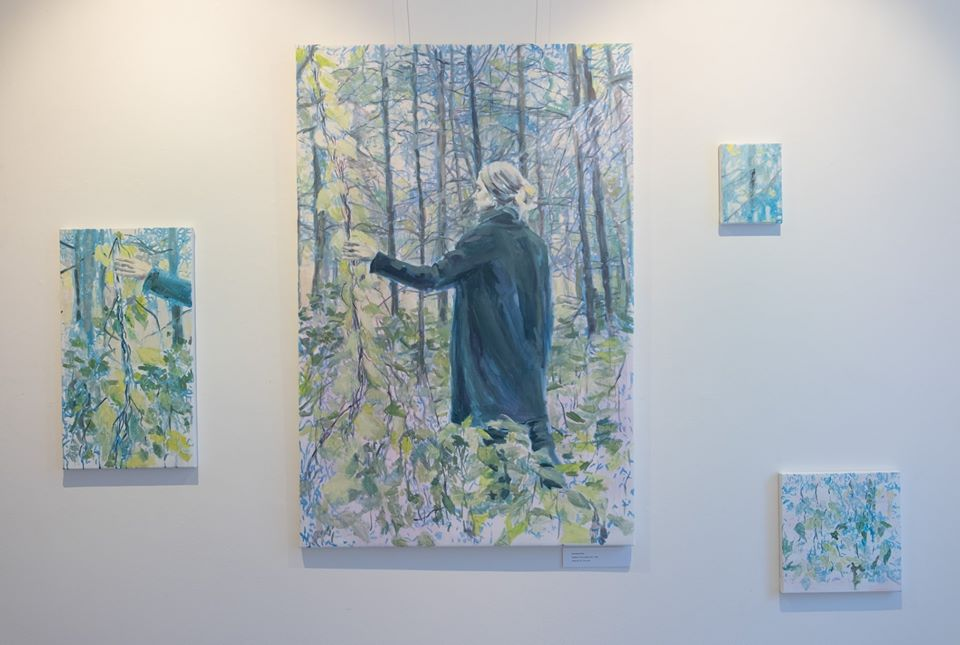 figurative painting of a young woman in a forest in exhibition