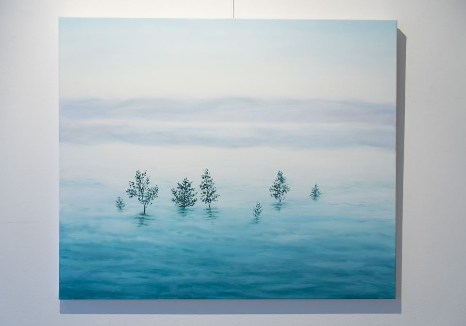 painting of a trees in water surrounded by fog hanging on a gallery wall