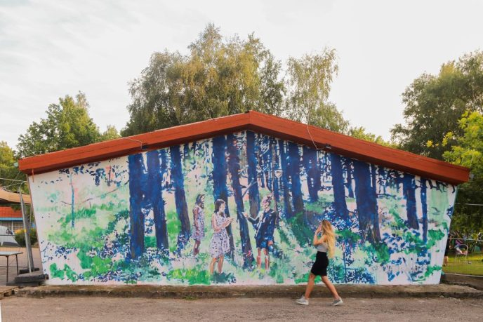 young female artist in front of the blue mural painting. two girls in a forest on a wall of cottage