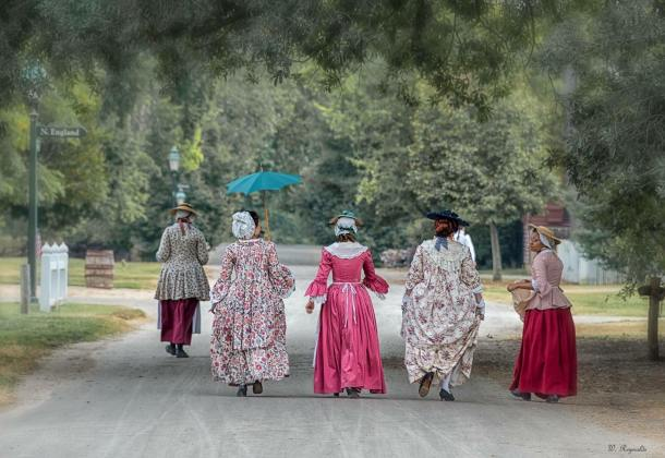 Women walk down a road in historical period dress in Colonial Williamsburg