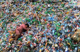 A recycling plant worker in China falls asleep on a pile of bottles. (Image from The Atlantic)