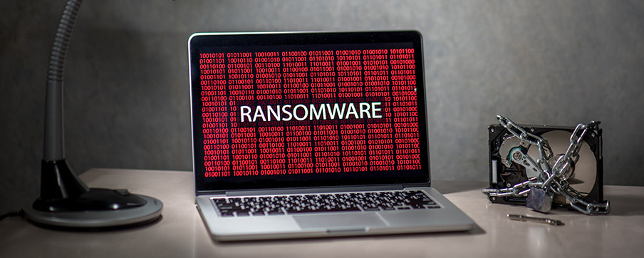 "A desk with a lamp, laptop and hard drive. The computer has the word ""Ransomware"" on it."