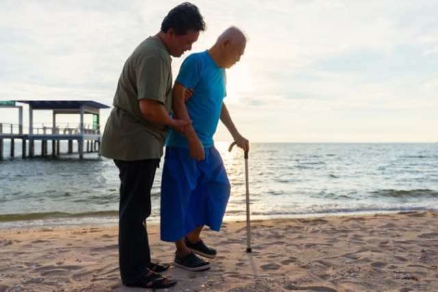 Son helping his senior father walk on beach