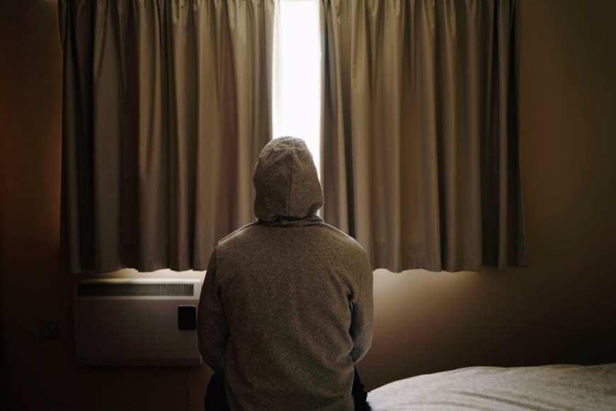 Man with Agoraphobia fear hiding behind curtains