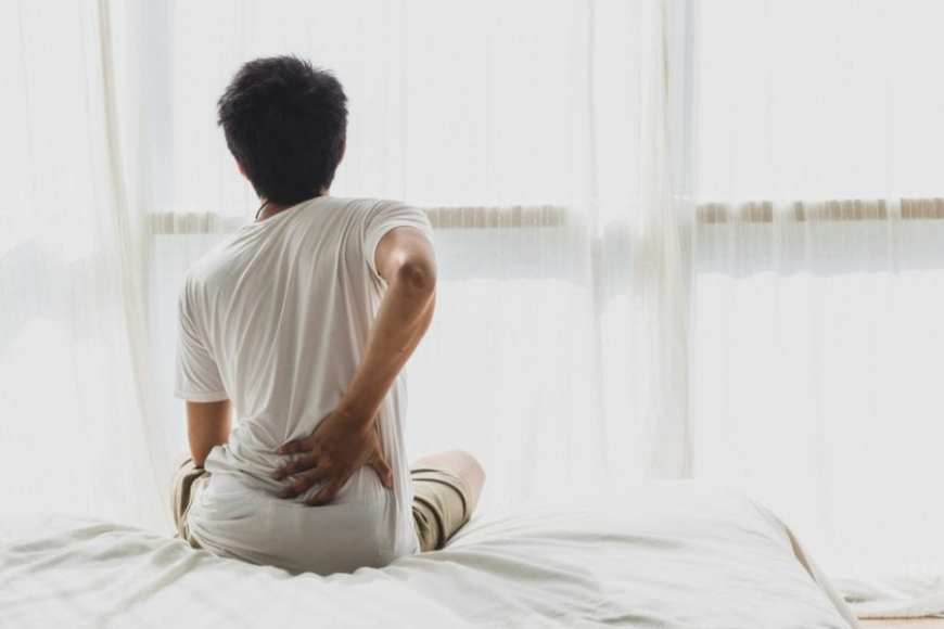 Man sitting on bed with back pain