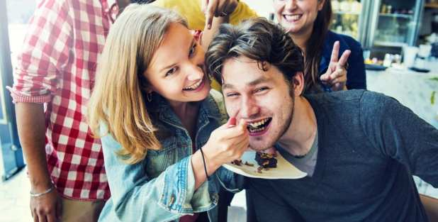 White Couple enjoying dessert as she feeds him cake