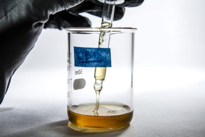 Beaker of CBD oil being testing by researcher in black glove