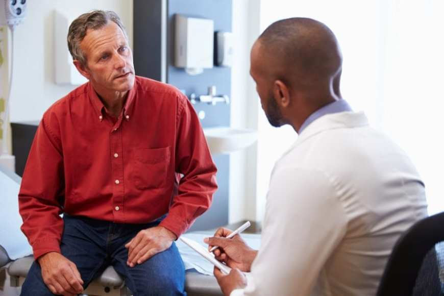 Elder Man consulting with young male doctor