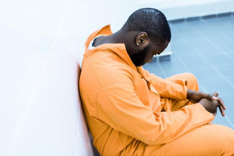 black man sad in jail and orange prison uniform