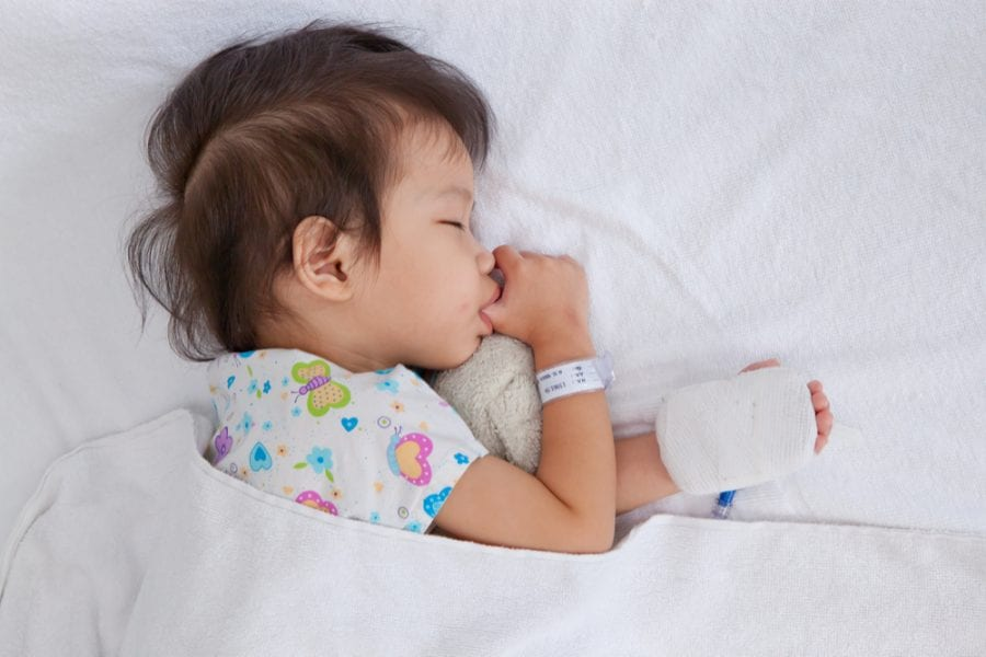 Sick child in hospital bed sucking thumb and sleeping