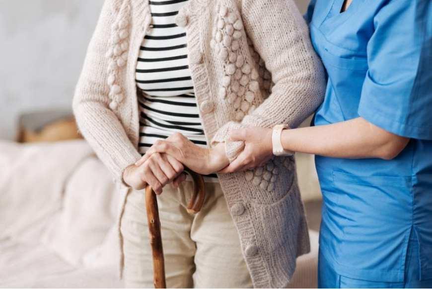 Elderly Woman being helped by nurse