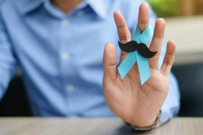 man hand holding up blue ribbon with moustache sticker