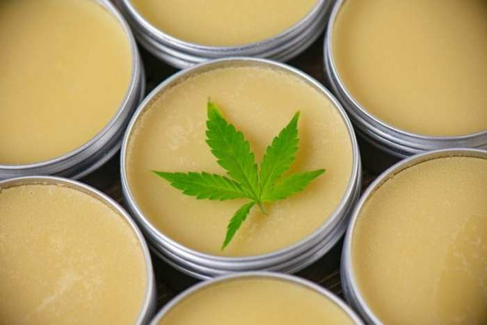 Close up of jars of cannabis topicals salve with cannabis leaf on top