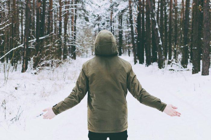 man in pine bush smelling terpenes