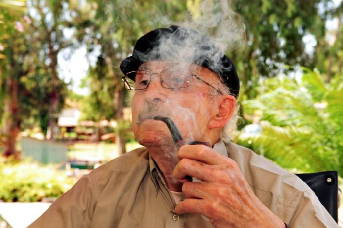 older adult smoking cannabis through a pipe