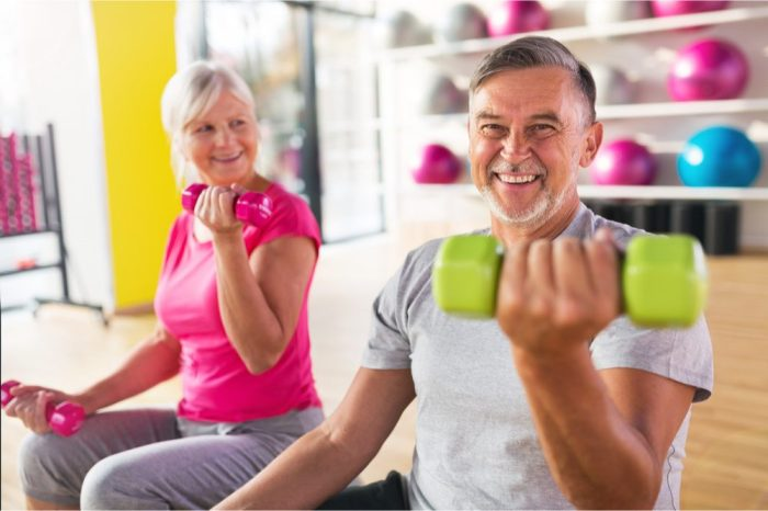 balanced health represented by older adults lifting small weights