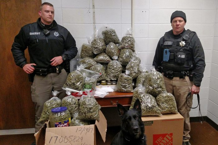 cannabis prohibition enforced by two police posing wiht bags of confiscated cannabis