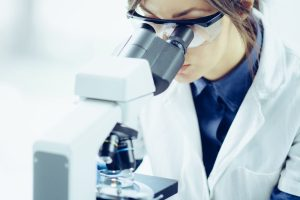 cannabis genome studied by young scientist looking into her microscope