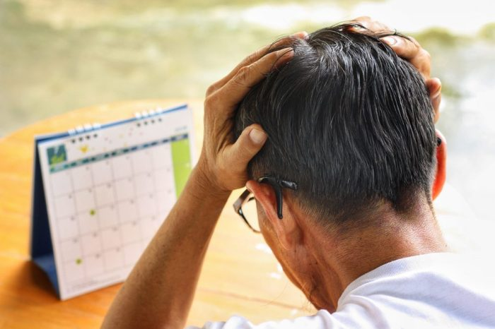 man possibly with cognitive impairment, looking at calender preplexed