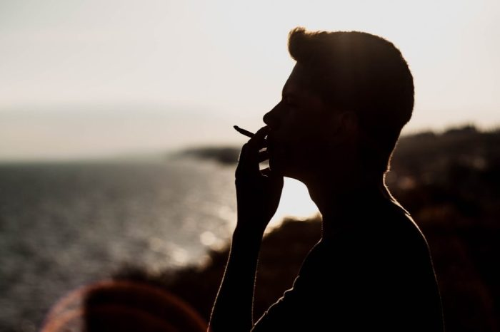 man smoking cannabis by the sea for his Crohn's Inflammation