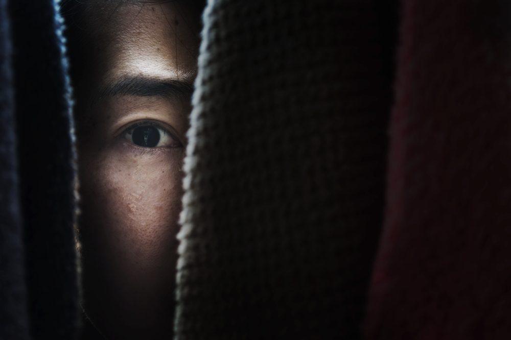 human trafficking represented by person peeking through door