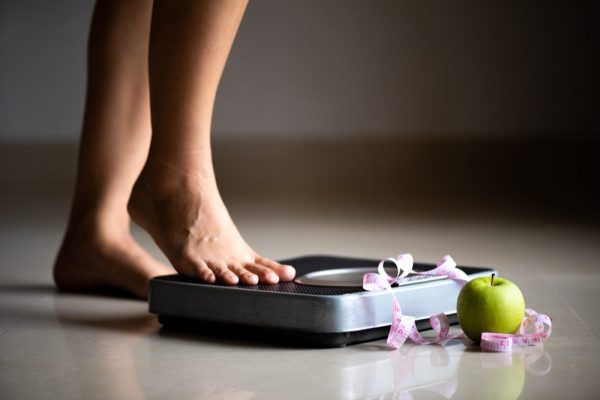 anorexia vs bulemia represented by bathroom scale, tape measure, and apple