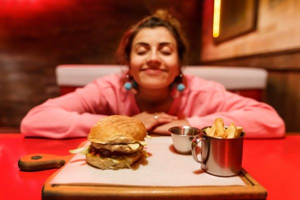 girl staring happily at hemp burger (possibly)