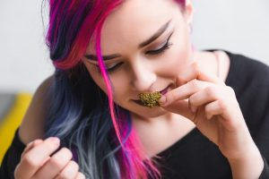 this young alternative woman sniffing her cannabis might be wondering how to fix wet weed