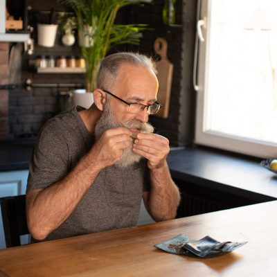 cannabis gear for older adults man rolling joint