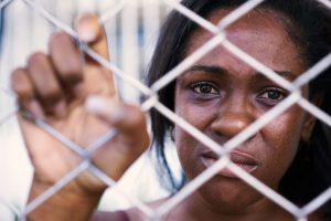 addiction in prison represented by young woman of african descent looking sadly through chain link fence