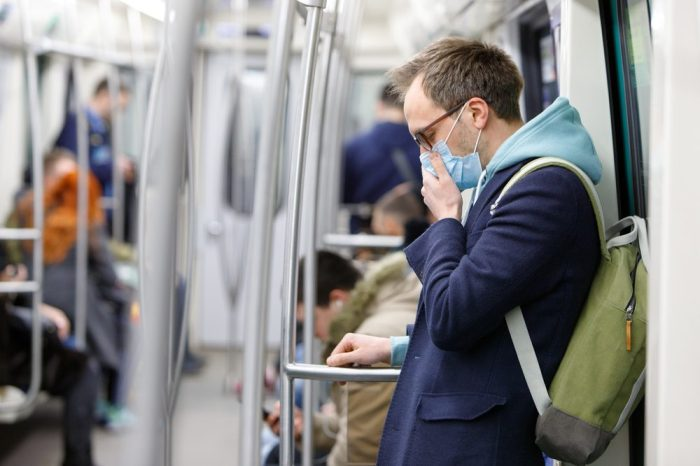 mental health and isolation represented by white man in mask on public transit