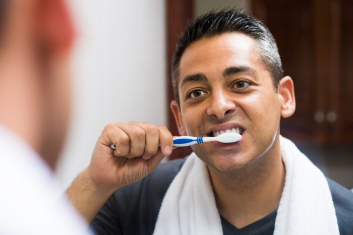 no rotten teeth for this man of east asian descent brushing in bathroom