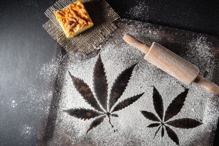 space cake represented by cannabis leaf designs in dough on baking table