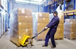 worker with stacker at warehouse