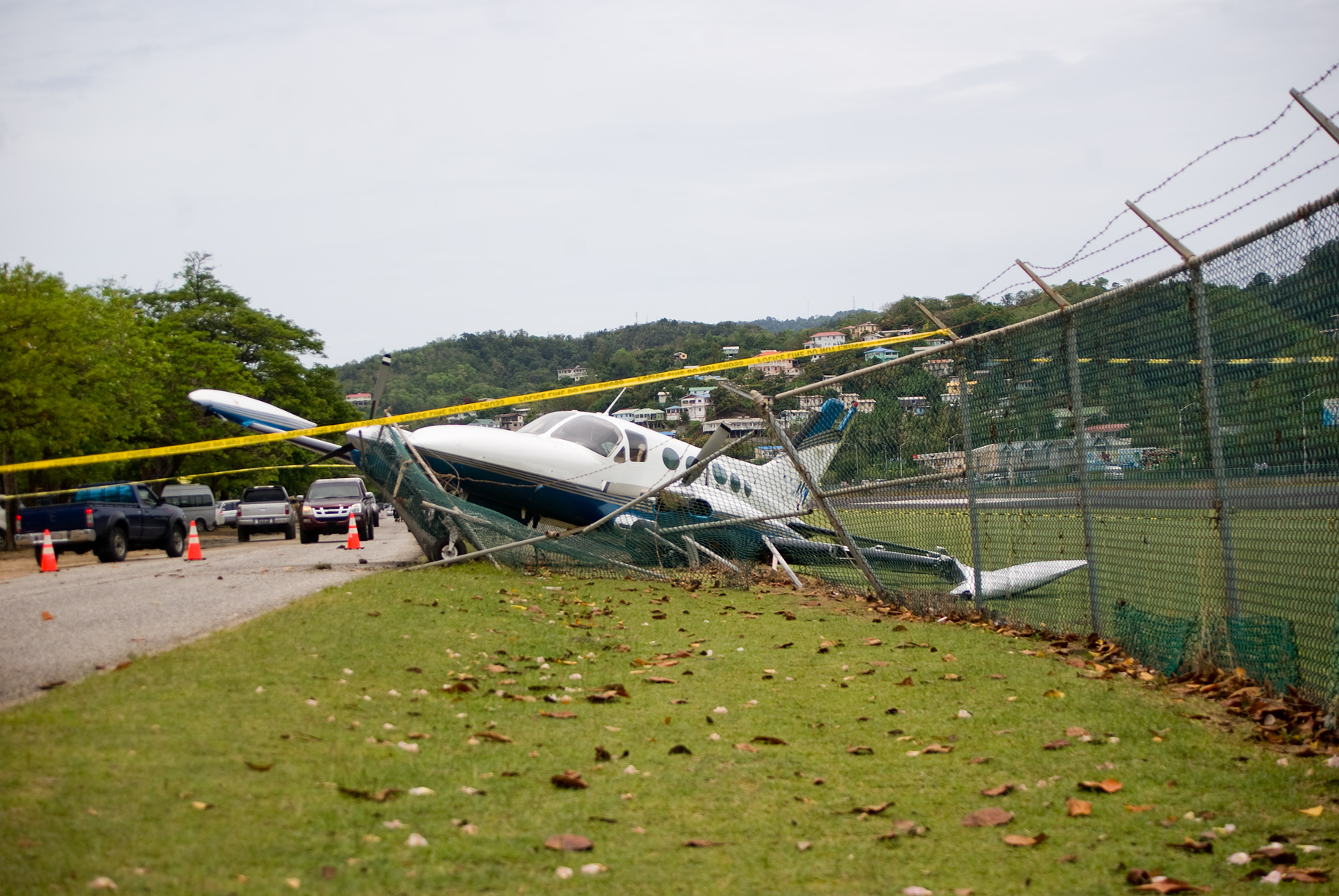 small plane crashes through fence on highway in emergency landing