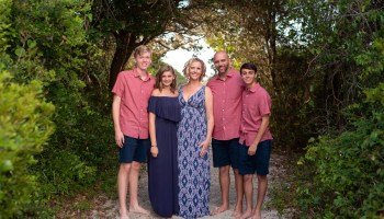 Family on the foliage covered walkway to the beach - Huntington Beach State Park