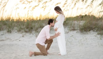 Maternity portrait - husband kissing wife on the belly - Huntington Beach State Park