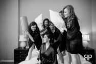 bride and her bridesmaids having a pillow fight