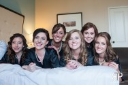 bride and bridesmaids on the bed