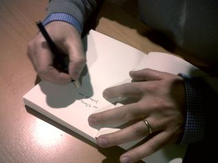 Andrea fa una dedica su una copia di Pelicula