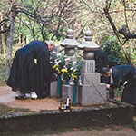 Photo of Tangen Roshi making an offering to Harada Roshi's grave