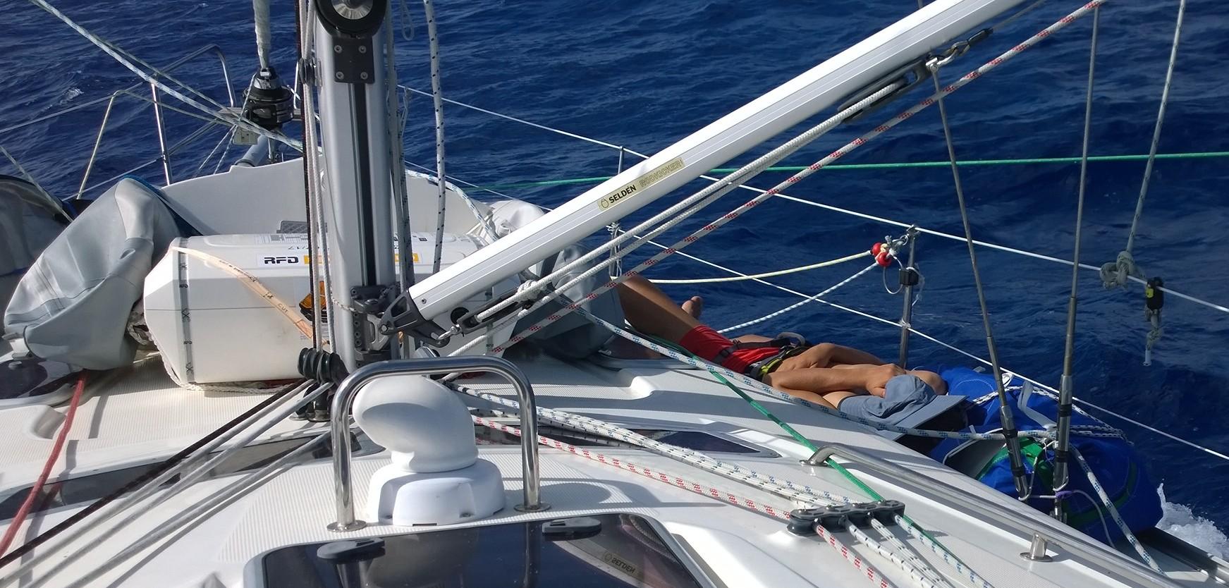 Veneessä voi torkahtaa monessa paikassa. Rimpiläinen nukkuu kannella purjeiden seassa.
