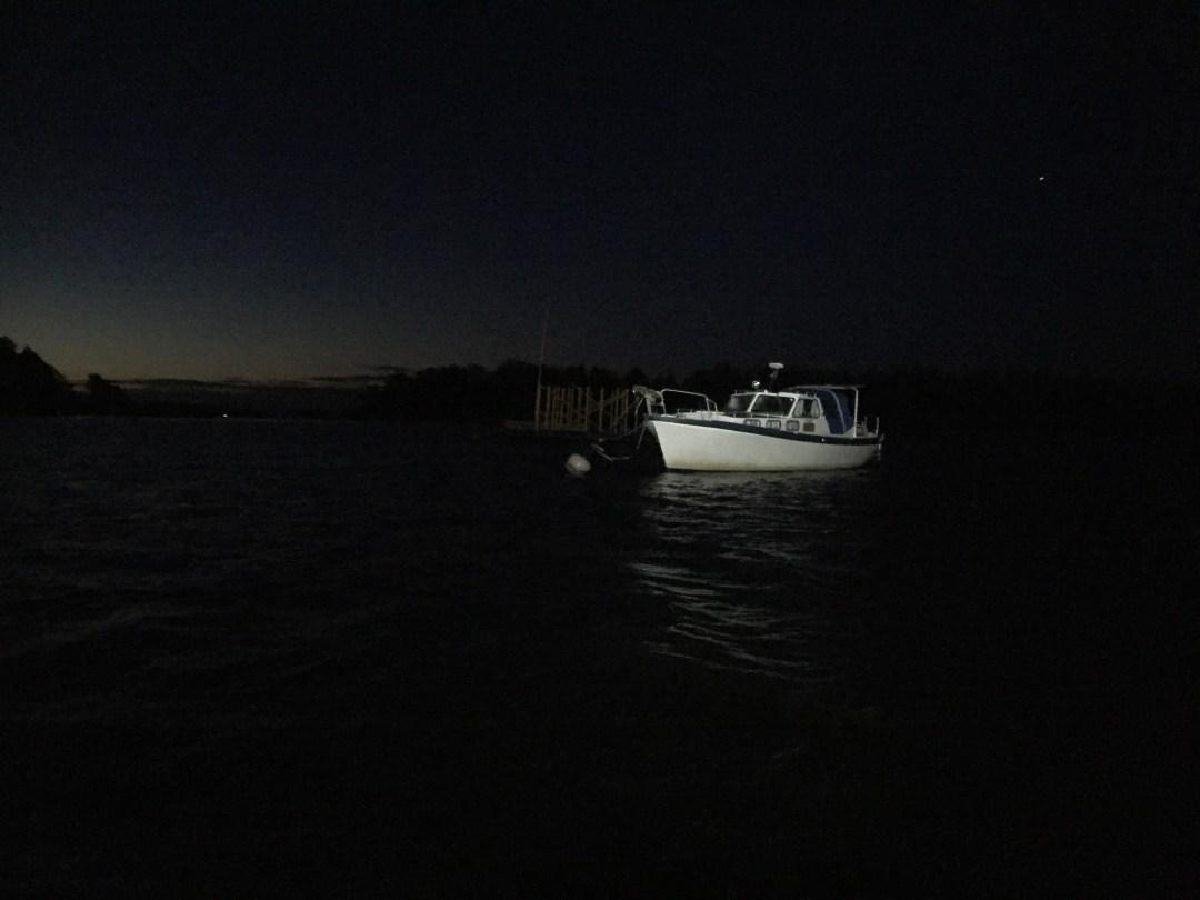 Matkan varrella on veneitä poijuparkissa. Niitä joutui pariin otteeseen tirailemaan kunnolla. Valkoinen veneen runko erottuu lampun valossa hyvin, mutta taustalla oleva keskeneräinen saunalautta ei kauas näy.