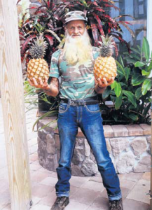 """Richard """"Tarzan"""" Hassell showing his """"record"""" pineapples."""