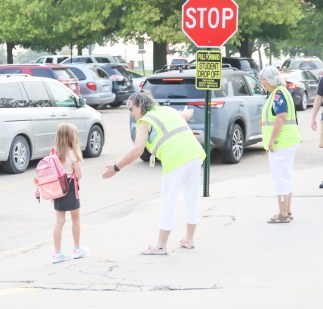 Lisa Baumgartner (left) and Susan Chandler (right) help guide a student on the first day of school on Thursday, August 19.