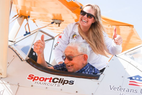 Kenny Chase and Allyssa VanMeter, a volunteer Crew Chief with Dream Flights, give a thumbs up after the biplane landed on Thursday, August 26.