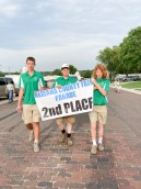Davis Rokey, Dane Haverkamp and John Langill walk with the second place banner, which was the Busy Jayhawkers 4-H Club during the Nemaha County Fair parade.
